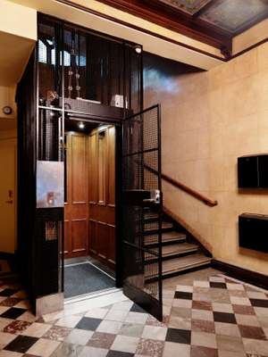 Wrought iron entrance to the wood-panelled lift in Block C