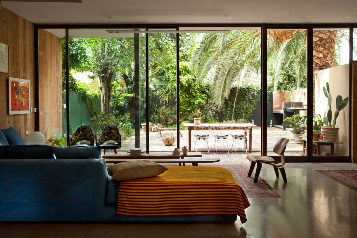 Living-room space on the open-plan lower floor looking on to the garden, complete with palm tree and parrilla (barbecue)