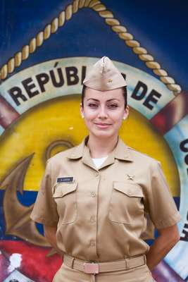 Naval officer Gloria García in front of Colombian colours