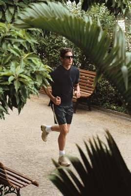 Hooded top by United Arrows, swimming trunks by Moncler, sunglasses by Thierry Lasry, socks by Hanes, shoes by Mizuno