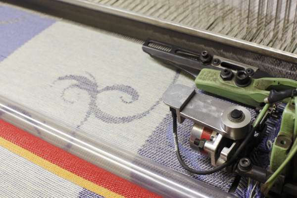 A jacquard fabric being woven