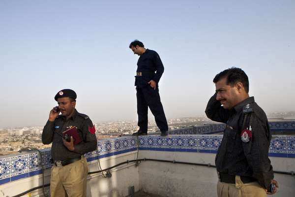 Policemen and a security guard on the roof of Karachi's Habib Bank Plaza