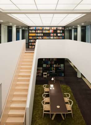 A white Gypsum barrier sweeps around the opening between the library's two floors, which are linked by a staircase in white stained ash.