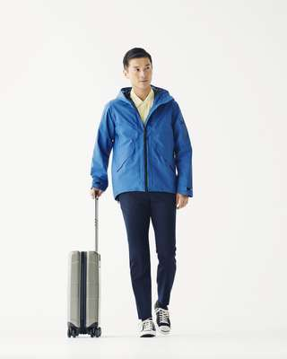 Jacket by Goldwin, shirt by Markaware from Parking, trousers by Auralee, trainers by Converse, suitcase by Victorinox