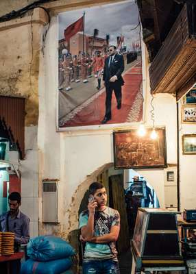 Making a phone call in the souk in Fes beneath an official poster of Mohammed VI