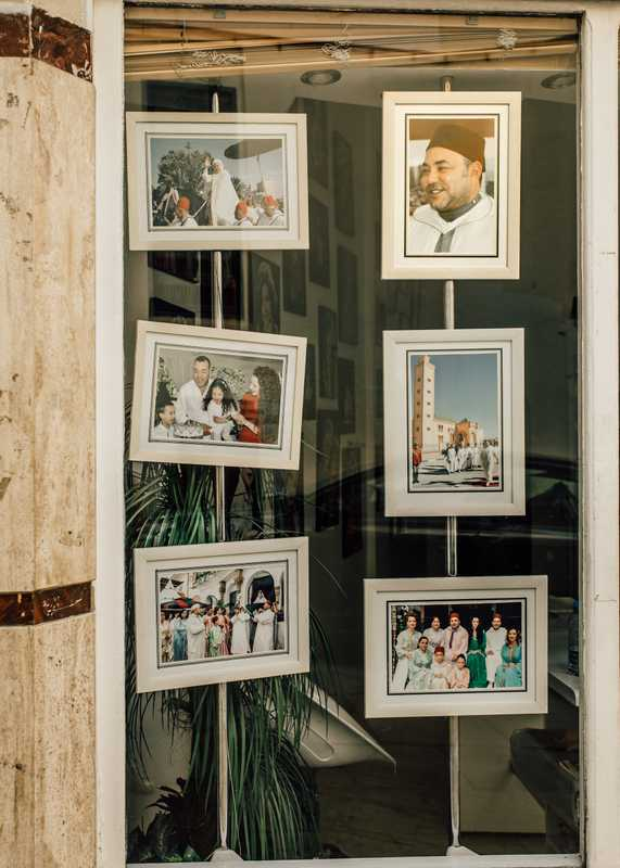 Multiple Mohammed VI portraits in the window of a Fes film developer