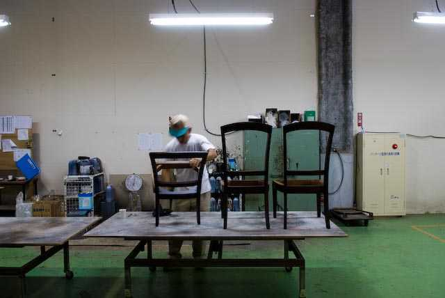 A worker checking the quality of chairs