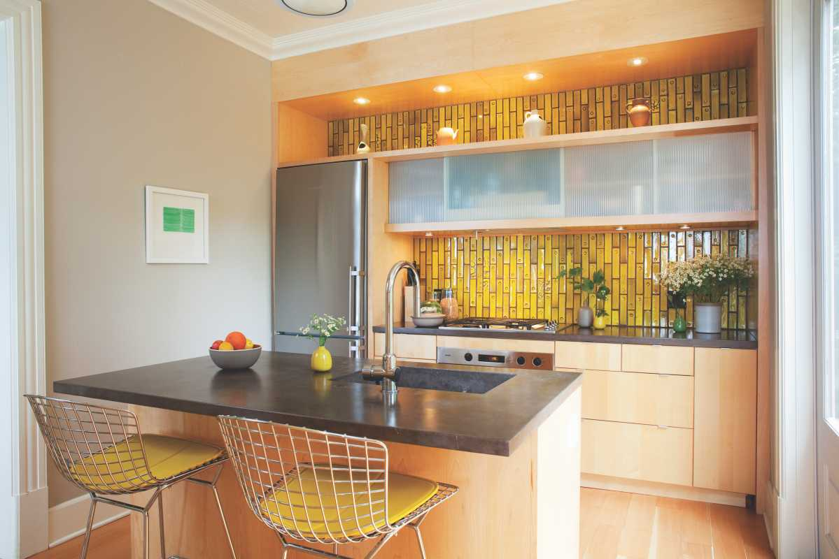 Kitchen with concrete counters and acid-yellow Heath tiles