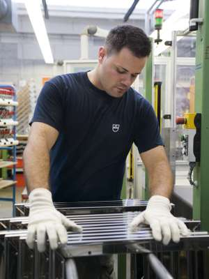 An engineer checks a stack of glass oven doors