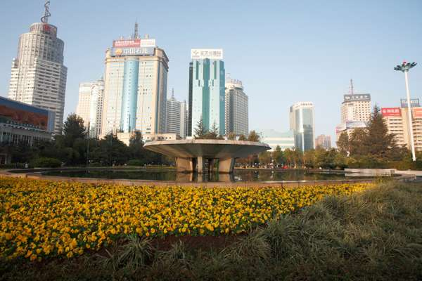 Fountain in Dong Feng Square with downtown Kunming in the background