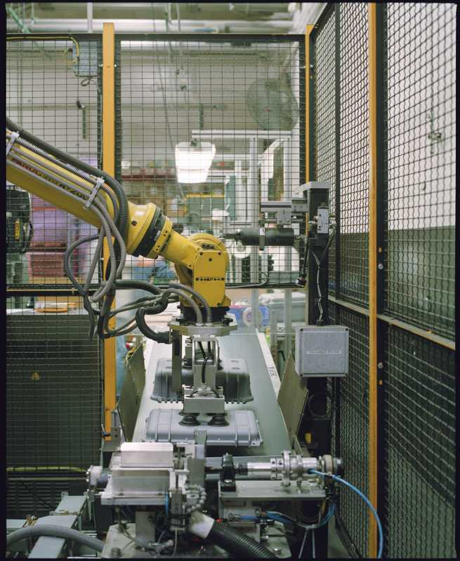 A robot drops cases onto the quality control and packaging line