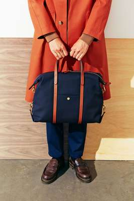 Coat by Tomorrowland × Mackintosh, jumper by Auralee, trousers by JW Brine, socks by Beams, shoes by Paraboot, bag by Mismo