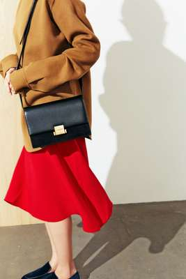 Highneck pullover by Jil Sander, skirt by Mansur Gavriel, bag by Saint Laurent by Anthony Vaccarello