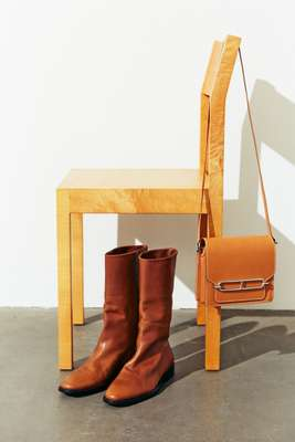 Boots by Saint Laurent by Anthony Vaccarello, bag by Hermès, chair by Nikari