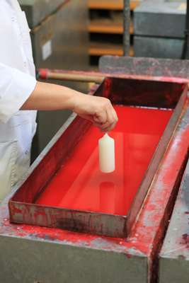 Dipping the pillar candles into dye