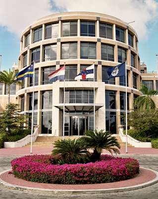 The bank, with flags of Curaçao, the Netherlands, Netherlands Antilles, and the central bank's crest