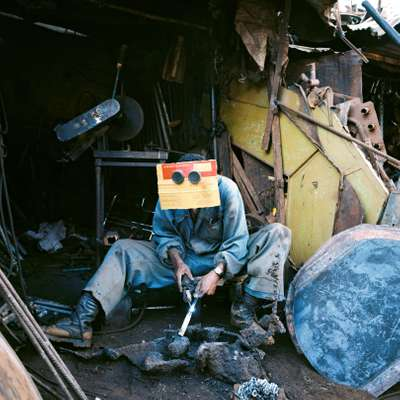 Ghilom Tesfamichael wears goggles and a piece of cardboard while welding at Medeber market