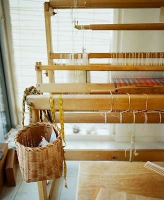Basket to catch clippings from weaving hangs on one of Sekimachi's looms