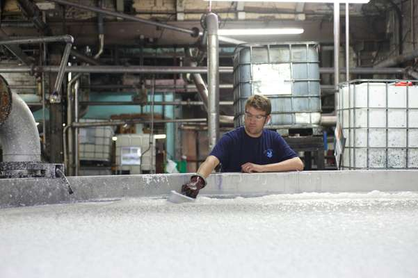 Worker checks the furnish (wet pulp) from the blending chamber