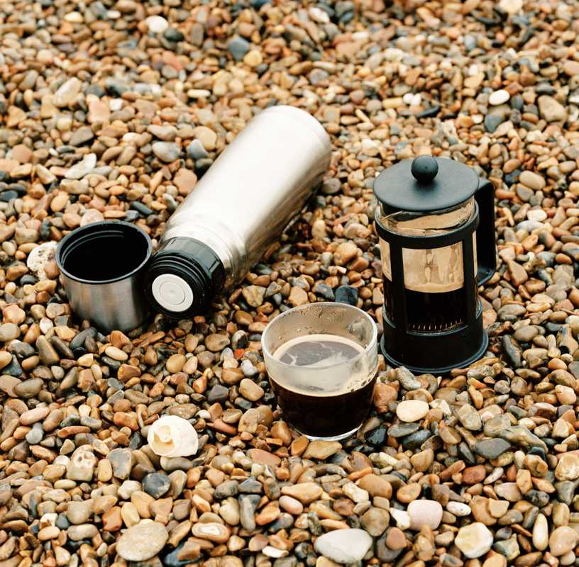 Fresh coffee brewed on the beach using hot water from the flask