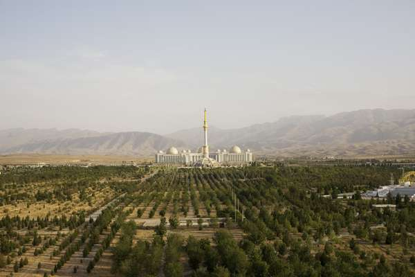 The monument to the independence of Turkmenistan across Independence Park. Behind are the Kopet Dag mountains, the border with Iran