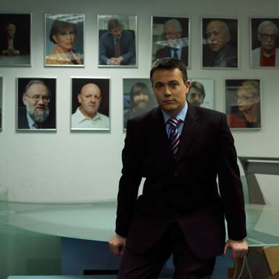 Presenter Kevin Owen in front of portraits of famous guests at the Russia Today studios