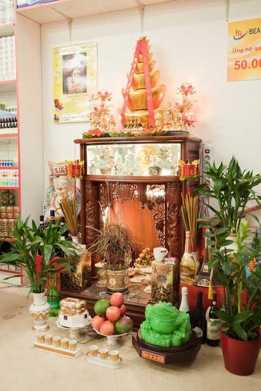 Buddhist shrine in Nguyen Thi Ha's store with offerings including fruit and alcohol