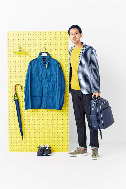 He wears: jacket by Brooksfield, jumper by John Smedley, jeans by Prada, trainers by Church's, backpack by Piquadro. On the board: watch by Cartier, jacket by Parajumpers, umbrella by Maehara Kouei Shouten, trainers by Woolrich