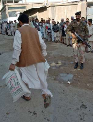 A soldier stands guard as people queue outside a flourmill in Karachi