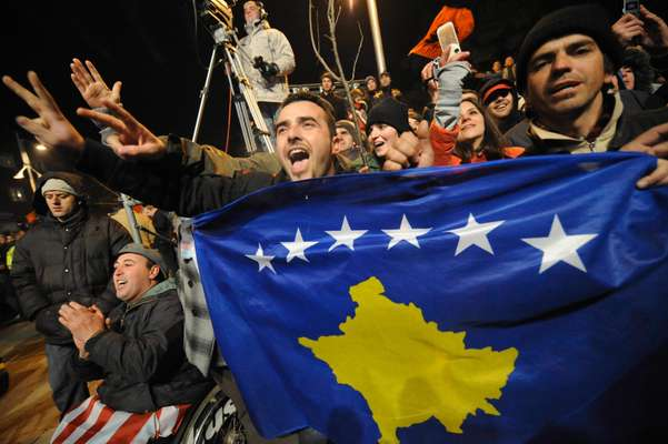 Kosovars display their new flag in the centre of Pristina