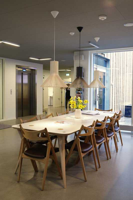 The reception/café area with chairs by Hans Wegner and lighting by Sector