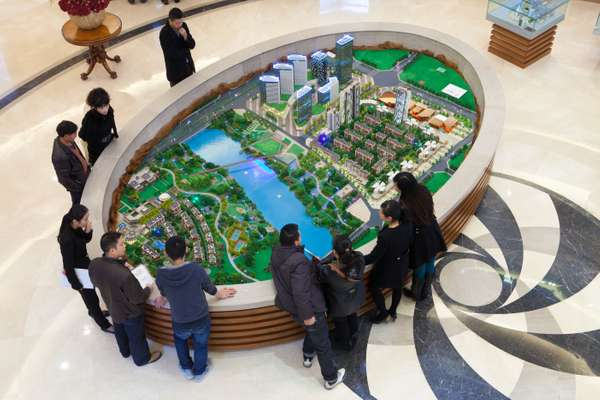 Prospective home buyers gather around a model of the Nordic City development