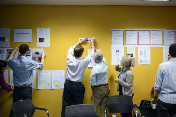 Redesign proposals are pinned to the wall during an innovation workshop