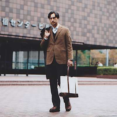 Jacket by Akamine Royal Line, trousers by Prada, jumper by United Arrows, shirt by Ermenegildo Zegna, shoes by Russell Moccasin for Nepenthes, coat by Hermès, bag by Porter