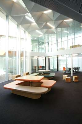 Lobby with G-shaped table and seating units. The low stools can be flipped on their side and turned into tables