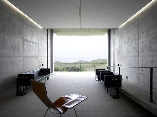 Sparse furniture and bare concrete contrasts with the exotic landscape