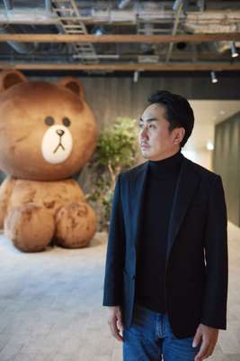 Line CEO Takeshi Idezawa, flanked by a giant version of Brown