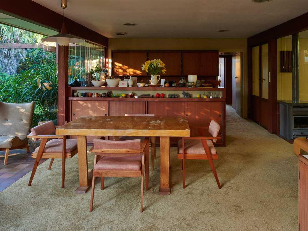 Open dining area that adjoins the kitchen; all cupboards are original