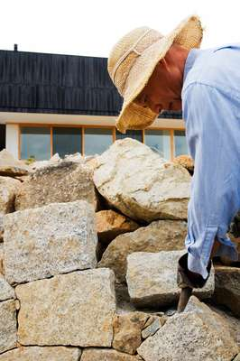 Owner Shigemi Asano building a stone wall