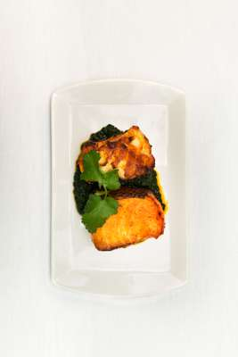 Masala sea bass topped with coriander and served on a spinach-and-mushroom base