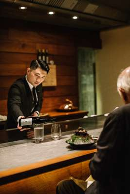 Pouring a glass of Masuizumi Platinum Nama saké