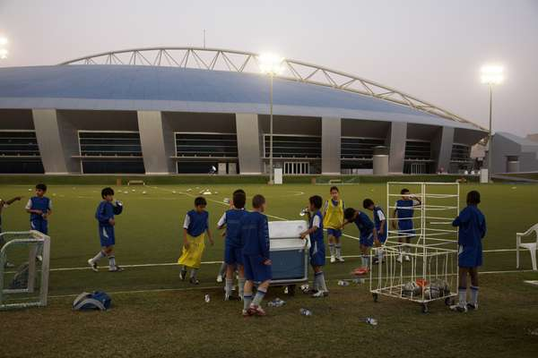 Students after evening football practice. The Aspire Dome is in the background