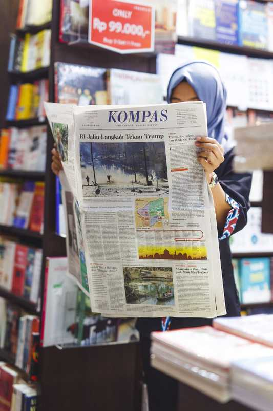 Indonesian woman reading 'Kompas' in the bookshop at Soekarno–Hatta International Airport