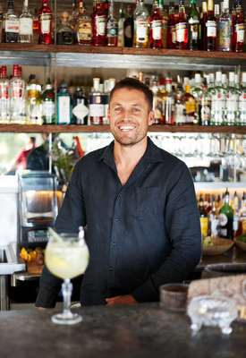 Jesse Williams mixing drinks  at his bar Paradiso