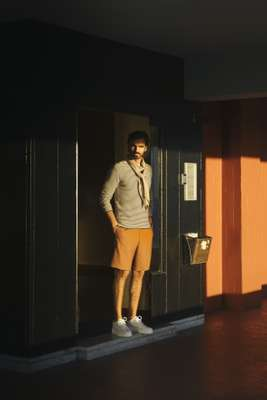 Jumper by Oliver Spencer, t-shirt by Scye, shorts by Tomorrowland, trainers by Bally, stole by ts(s)