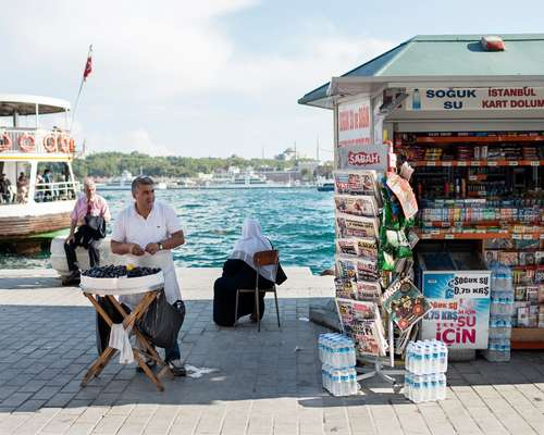 'Midye' (mussels stuffed with rice) for sale and a newspaper kiosk