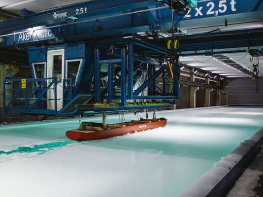 A scale model icebreaking cargo ship is tested in the Aker Arctic facility