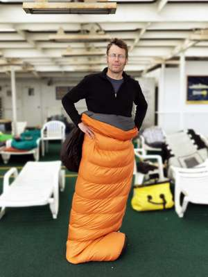 A passenger models his sleeping bag