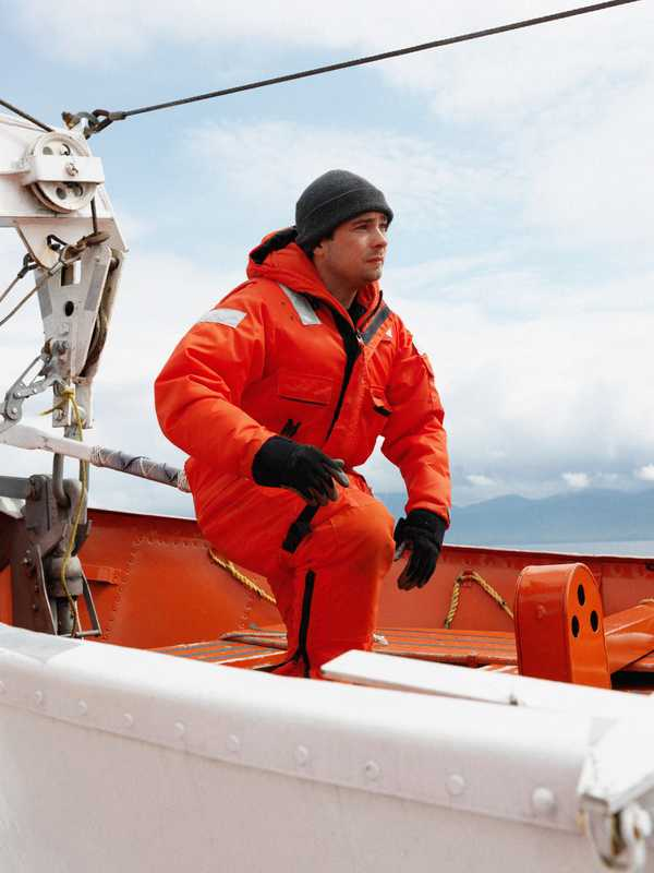 A crew member dons a float suit for a safety drill