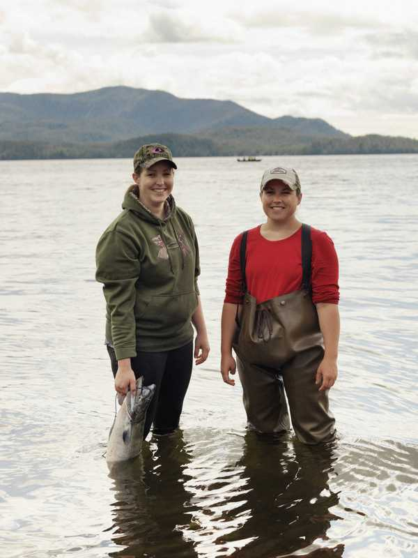 Women in hip waders clean fresh-caught salmon